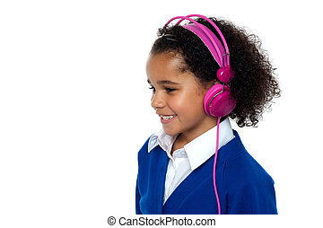 Charming young kid listening to music