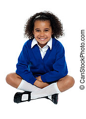 Charming African school girl flashing a smile. Studio shot