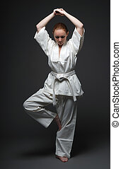 Girl in white kimono, traditional stance of aikido