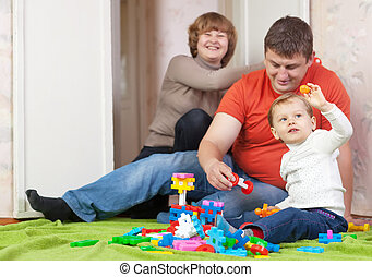 child plays with meccano set in home