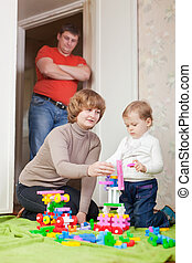 parents and child plays with meccano set in home