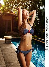 Beautiful tan woman in bikini sunbathing