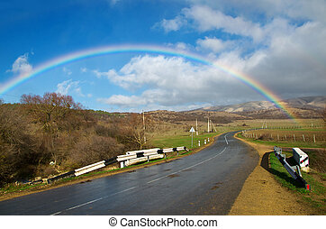 rainbow - Full rainbow over road against the clouds at...