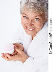 Skin care - Elderly woman with cream on a white background