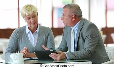 Tablet presentation - Senior man making a presentation using...