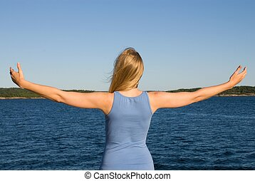 a young woman at the sea with arms wide open - a young...