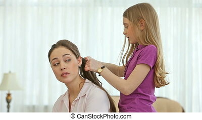 Little hairdresser - Pretty little girl doing her sister's...