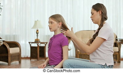 Home salon - Girl combing and braiding her little sisters...