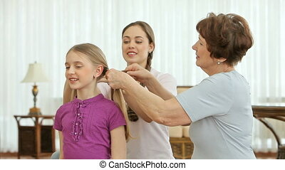 Hair care - Women of different age braiding the hair of a...