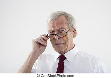 Handsome retired man in glasses peering over the top of the...