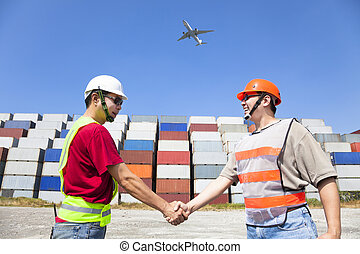 two happy workers handshaking before transportation...