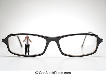 Diminutive elderly man peering through spectacles -...