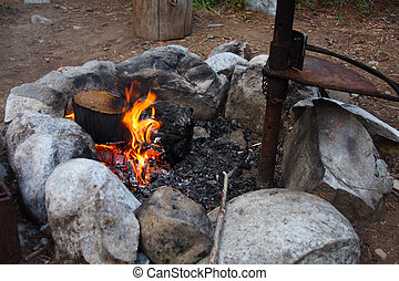 Campfire Ring - Burning campfire with grill surrounded by...