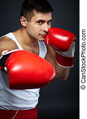 Male boxer - Portrait of young man in red boxing gloves...