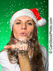 Girl in a Christmas hat blows off snowflakes on green...