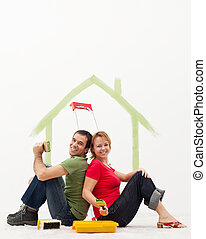 Young couple in their new home painting