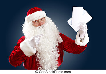 santa claus reading a letter - Santa Claus holding and...