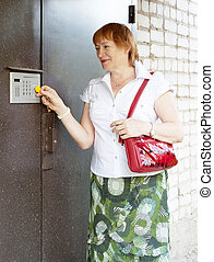 woman opening door with electronic key - Mature woman...