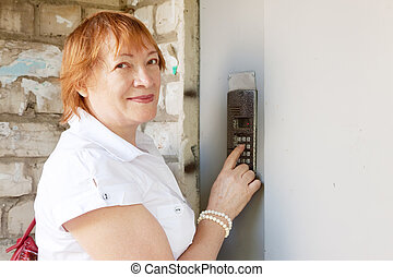 woman pushing button of house intercom - Mature woman...