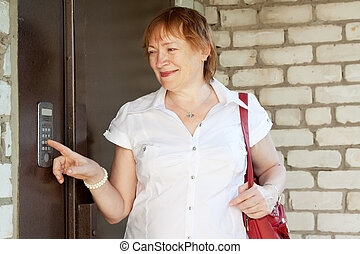 woman pushing button of intercom - Mature woman pushing...