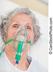 Elderly woman with an oxygen mask in a hospital looking away