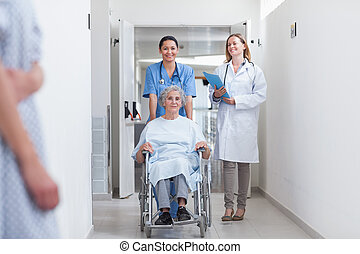 Smiling nurse assisting senior woman sitting in a wheelchair...