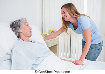 Smiling woman holding the hand of a patient in a room -...