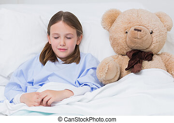 Child sleeping with a teddy bear while lying in a bed -...