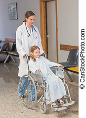 Doctor wheeling a patient in a wheelchair