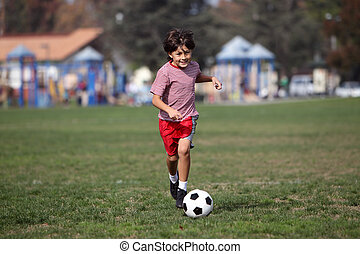 Boy playing soccer n the park