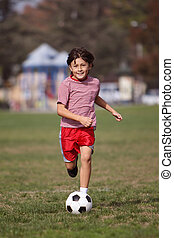 Boy playing soccer in the park - running towards camera -...