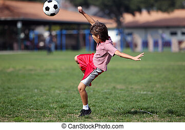 Boy playing soccer or football in the park - landscape...