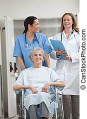 Nurse wheeling a patient in a hallway