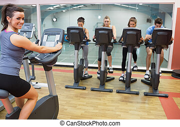 Smiling woman teaching spinning class to four people in gym