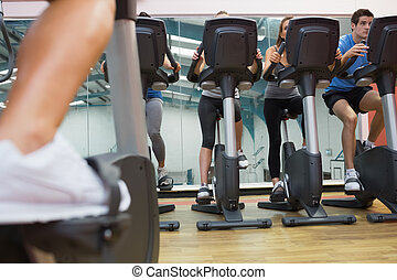 People taking a spinning class - Four people taking a...