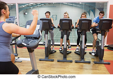Enthusiastic woman teaching spinning class to four people at...