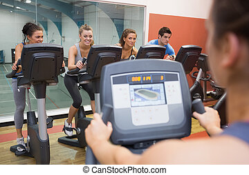 Smiling group taking spinning class at the gym