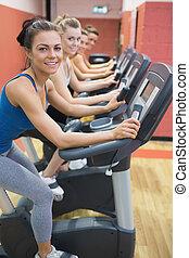 Four women on exercise bikes