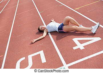 Woman taking break on track field - Woman lying down taking...