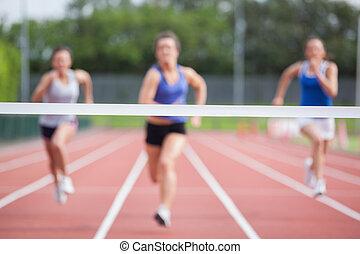 Athletes racing towards finish line - Female athletes racing...