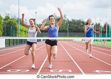 Athletes celebrating as they cross finish line - Female...