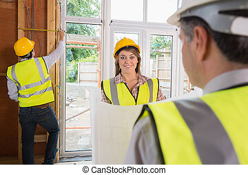 Woman smiling at architect while man is measuring