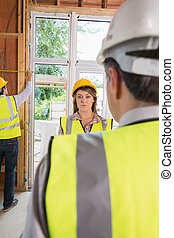 Woman looking upset at architect while man is measuring
