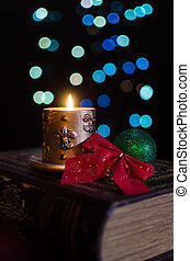 Burning candle and seasonal decorations on bokeh lights...