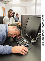 Man taking nap at computer class on the keyboard in college