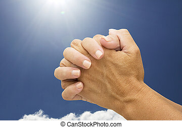 Praying Hands - Female hands praying with a sky background,...