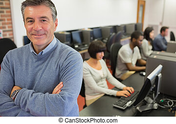 Teacher smiling at top of computer class in college