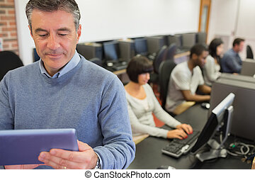 Teacher standing holding a tablet PC in computer class in...
