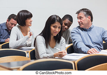 Students talking in lecture - Mature students talking in...