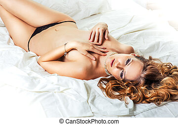 Young sexy woman on bed